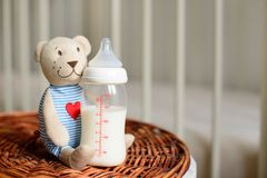 Bottles with milk for baby and bear toy on a straw basket. Stock Images