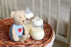 Bottles with milk for baby and bear toy on a straw basket. Kids room with a bed. Royalty Free Stock Image