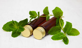 Bottles of mint oil and fresh mint. On a old wooden background Royalty Free Stock Photo