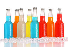 Bottles of multi-color drinks with ice on white Stock Photos