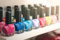 Bottles of multi-colored beautiful nail polish, placed in a row on a wooden shelf stock images