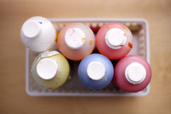 Bottles of multi-coloured paints, close-up, overhead view (still life, differential focus) Stock Photos
