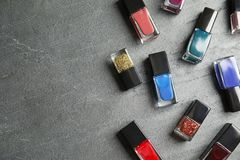 Bottles of nail polish on grey background, top view. With space for text stock photography