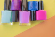 Bottles of nail polish. A group of bright nail polishes on a colored, yellow background stock image