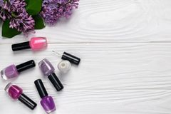 Bottles of nail polish on white wooden background with spring flowers top view with space for text royalty free stock image