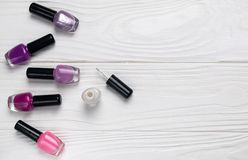 Bottles of nail polish on white wooden background top view with space for text royalty free stock image