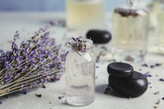 Bottles with natural herbal oil and lavender flowers on color table. Closeup stock image