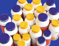 Bottles of nutritional supplements. Isolated on blue Royalty Free Stock Image
