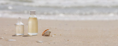 Bottles with oil essence and shell in the sea waves. Spa and wel Stock Photo