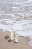 Bottles with oil essence and shell in the sea waves. Spa and wel Stock Photography