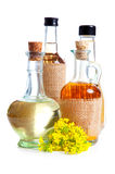 Bottles of oil with rapeseed flower Stock Photos