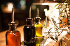 Bottles of oil. With tips standing on wooden table with oil tree Royalty Free Stock Images