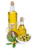 Bottles of olive oil and green olives with leaves Stock Images