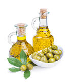 Bottles of olive oil and green olives with leaves Royalty Free Stock Images