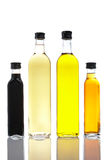 Bottles of olive oil and vineg. Several bottles of olive oil and vinegar reflected on white background Stock Photography