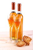 Bottles of passito wine. On pine floor varnished with goblets and pastries on white background Stock Photos