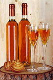 Bottles of passito wine. On pine tree trunk with goblets and pastries on background made with pine wood Royalty Free Stock Image