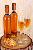 Bottles of passito wine. On pine tree trunk with goblets and pastries on background made with pine wood Stock Image