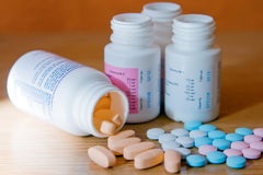 Bottles and Pills. Closeup pink, white, blue and orange vitamins with bottles Royalty Free Stock Photography