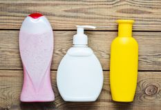 Bottles of products for the bathroom. Shower gel, liquid soap, shampoo on a wooden table. Top view Royalty Free Stock Photos