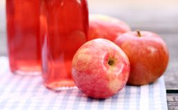 Bottles with red drinks and some apples. Two bottles with red drink and some apples near by on a napkin Royalty Free Stock Photo