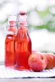 Bottles with red drinks and some apples Stock Images