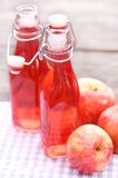 Bottles with red drinks and some apples. Two bottles with red drink and some apples near by on a napkin Stock Photos