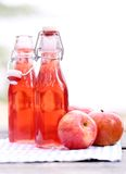 Bottles with red drinks and some apples. Two bottles with red drink and some apples near by on a napkin Royalty Free Stock Image