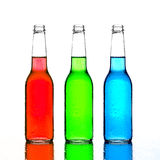 Bottles red green and blue with reflection. Bottles with red, green, and blue liquid on wet reflective surface on white Royalty Free Stock Images