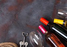Bottles of red white and pink rose wine with glasses and corkscrew opener on stone kitchen table background. Top view. Space for t stock photo