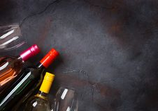 Bottles of red white and pink rose wine with glasses on stone kitchen table background. Top view. Space for text stock photography