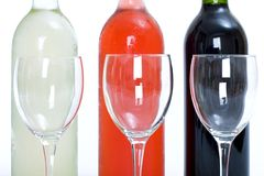 Bottles of red, white and rose wine with glasses royalty free stock photography