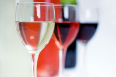 Bottles of red, white and rose wine with glasses in front royalty free stock images
