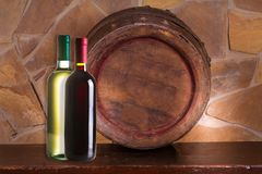 Bottles of red and white wine, old wine barrel in cellar. Space for text stock image