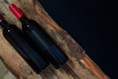 Bottles of red wine composed on wooden logs above black background.  royalty free stock images