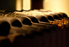 Bottles of red wine on a shelf. Bottles of red wine on a wooden shelf Royalty Free Stock Image