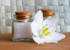 Bottles of sea salt and oil with white flower Royalty Free Stock Photo