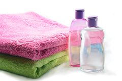 Bottles of Shampoo and Oil with Towels. Bottles of Shampoo and Oil with Pink and Green Towels Stock Photo