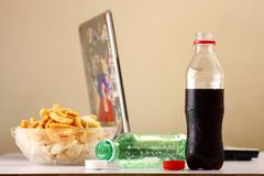 Bottles of softdrinks or soda, chips and a laptop computer in the background Royalty Free Stock Photography