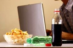 Bottles of softdrinks or soda, chips and man working on a laptop computer in the background Stock Image