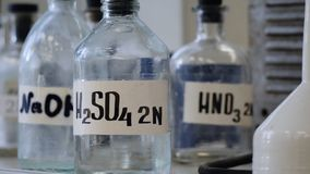 Bottles of solutions stored on shelf in laboratory. Bottles with chemical solutions of NaOH, H2so4 and HNO3. Sulfuric royalty free stock photography