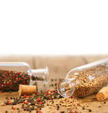 Bottles of spices on rustic table Stock Images