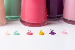 Bottles with spilled nail polish. Over white background Royalty Free Stock Image