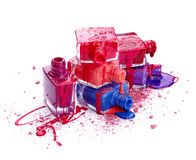 Bottles with spilled nail polish and crushed eye shadow. Isolated on white background Royalty Free Stock Photography