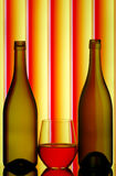 Bottles & stemless wine glass. Two bottles and a stemless wine glass filled with red wine on striped colorful background royalty free stock images