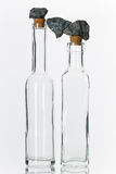 Bottles with stones. Grey stones in balance on glass bottles on white ground Stock Images