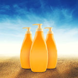 Bottles of Sunbath oil or sunscreen. On hot beach sand in summer royalty free stock photography