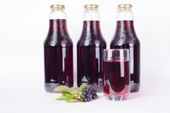 Bottles of syrup made from chokeberry and glass Royalty Free Stock Images