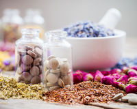 Bottles of tablets, healing herbs and mortar with lavender Royalty Free Stock Photo