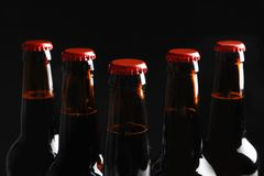 Bottles of tasty cold beer on black background, closeup royalty free stock photo